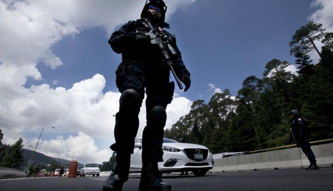 """Un agente federal patrulla un retén al oeste de la Ciudad de México. Las autoridades mexicanas han instalado retenes en carreteras, aeropuertos y fronteras en busca de Joaquín """"El Chapo"""" Guzmán. (AP/MARCO UGARTE)"""