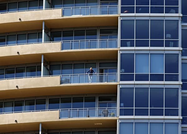 A man watched the police activity below from a balcony.