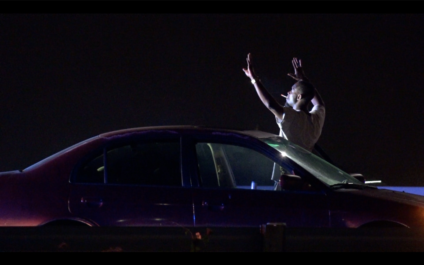 A suspect holds up his hands before he was taken into custody after leading law enforcement agencies on a 15-minute chase Saturday morning that started in northwest Dallas and ended near Garland.