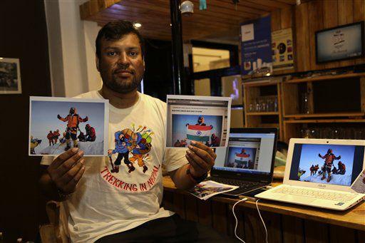 El alpinista Satyarup Sidhantha muestra en su mano derecha una fotografía donde sale él en la cima del monte Everest, y en la otra mano una foto que él asegura fue alterada por una pareja india para parecer que llegaron a la cumbre, el 4 de julio de 2016, en Calcuta, India. /AP