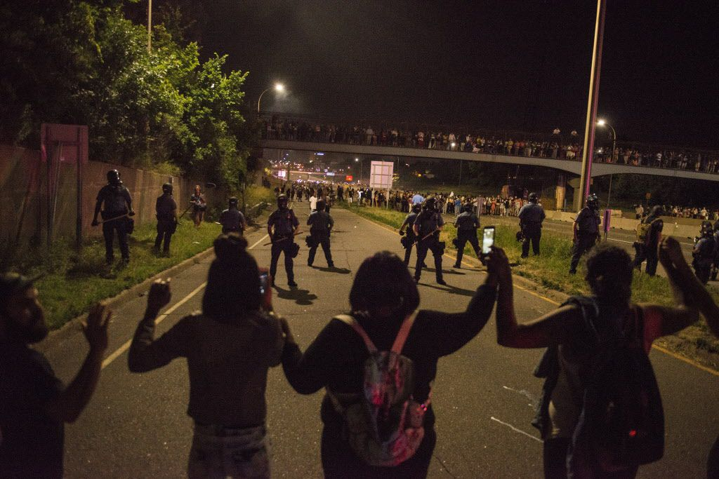 Protesters link hands after shutting down Interstate 94 in St. Paul, Minn.