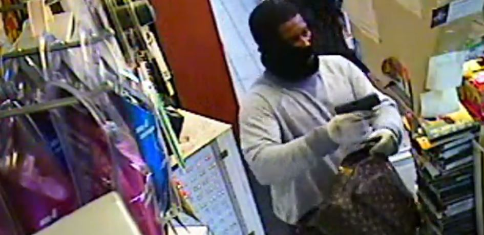 One of two suspects in a robbery of a Mesquite convenience store pulls a gun on a clerk during the robbery Wednesday.