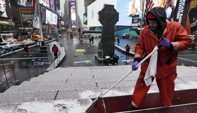 Francisco Mathurine limpia los escalones de la plaza Father Duffy, en Nueva York. La ciudad se prepara para una nevada histórica que podría paralizar la vida cotidiana. (AP/Richard Drew)