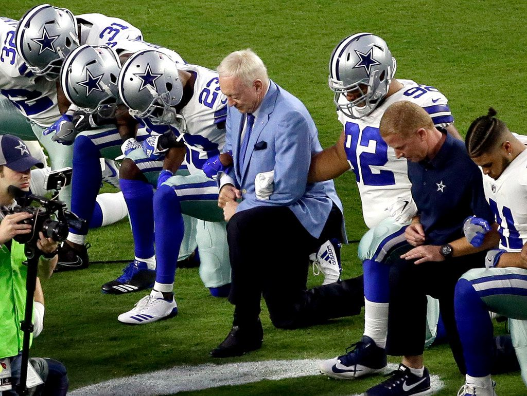 The Dallas Cowboys, led by owner Jerry Jones, took a knee prior to the national anthem Monday night. (Matt York/The Associated Press)