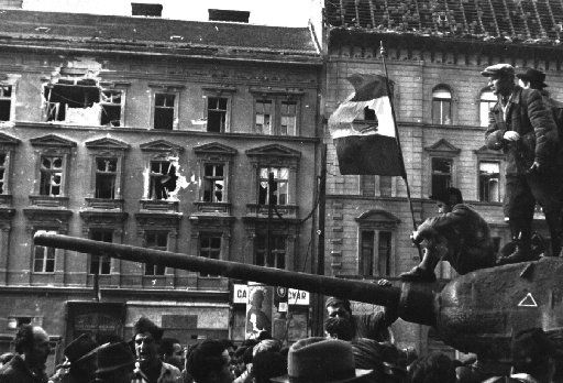Freedom fighters sat atop a tank with a revolutionary flag in Budapest during the uprising against the Soviet-supported Hungarian communist regime in 1956.