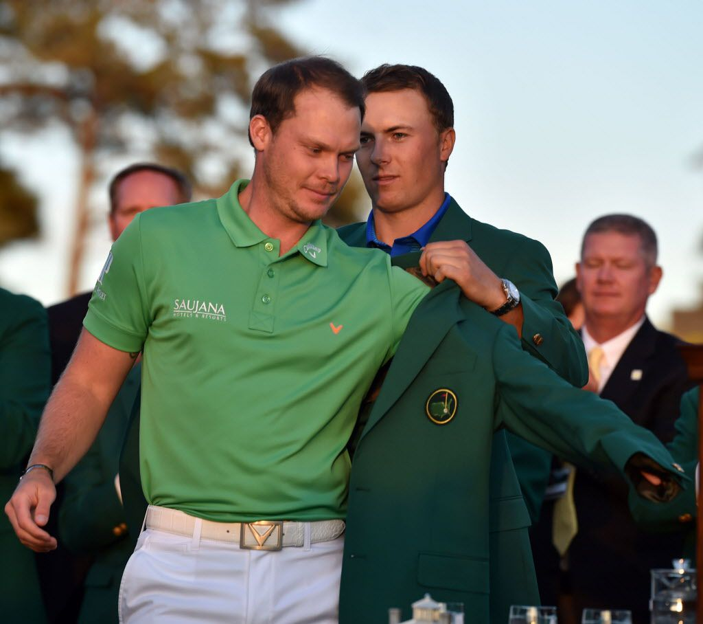 Masters champion Danny Willett gets the Green Jacket from Jordan Spieth following the final round of the 80th Masters on Sunday, April 10, 2016, at Augusta National Golf Club in Augusta, Ga. (Brant Sanderlin/Atlanta Journal-Constitution/TNS)