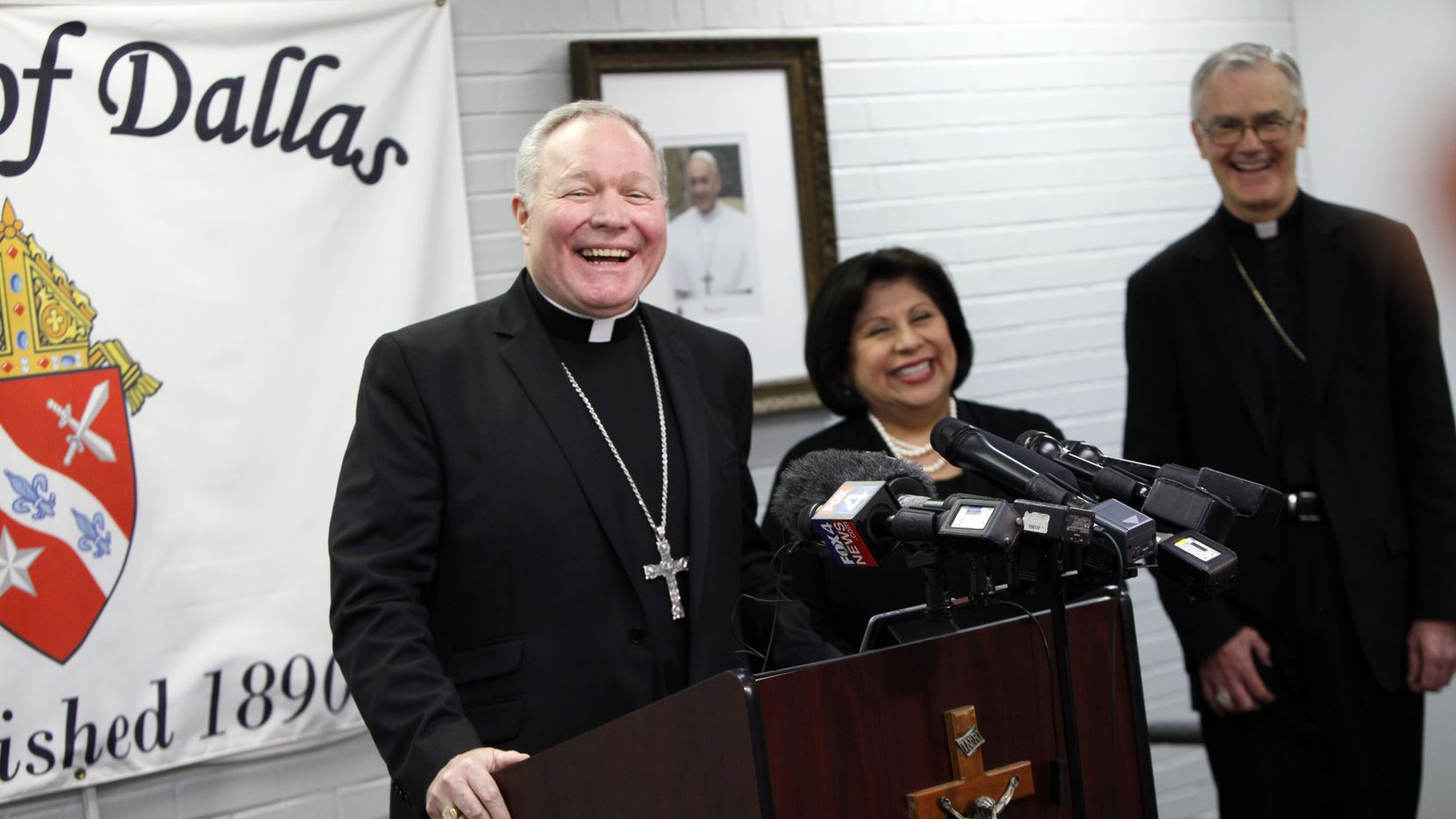 The Most Reverend Edward J. Burns speaks during a press conference as he's introduced as the new Bishop of Dallas at the Diocese offices in Dallas on Dec. 13, 2016. At right of the Bishop is the Director of Communications Annette Gonzales Taylor and Dallas Auxiliary Bishop John Gregory Kelly.