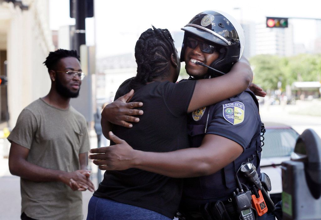 In this June 30, 2017, photo, Shetamia Taylor hugs Dallas Area Rapid Transit Police Officer Anthony Rhodes, right, as her son Kavion, left, watches in Dallas. Rhodes is the officer who drove Taylor to the hospital after she was shot during a sniper attack at a Black Lives Matter protest on July 7, 2016.