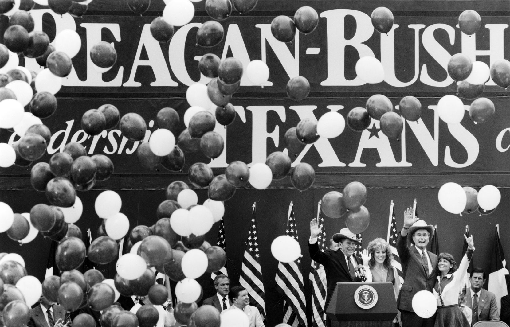 1984: President Ronald Reagan and Vice President George H. W. Bush wave to a crowd of supporters at the end of their rally in Austin. The cheerleaders shown presented them with cowboy hats.