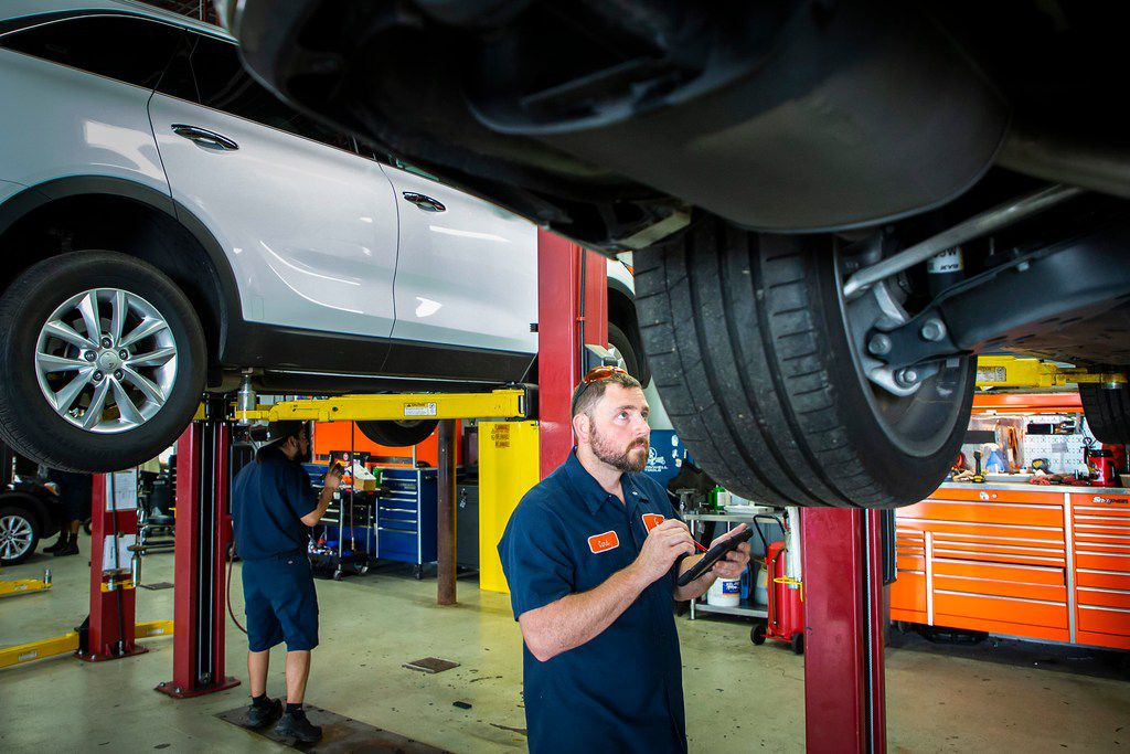 Carl Brown (front) and Efrain Banuelos inspect vehicles at driversselect in Grand Prairie.