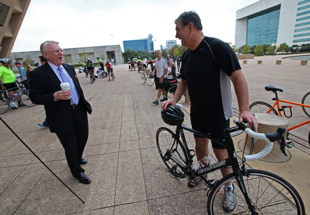 Mayor Mike Rawlings is greeted by John Crawford, president of Downtown Dallas Inc., (left) after a ride to City Hall to dramatize their drive to make Dallas more bike friendly.