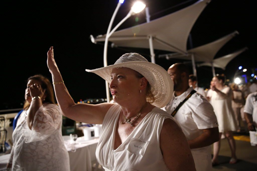 Vicki Capers struts to a song during the inaugural Diner en Blanc Dallas on the Continental Avenue Bridge in Dallas on Sept. 17, 2015. Exactly 1,678 people attended the event, which requires dinner guests to dress all in white and bring their own chairs and centerpieces. As per tradition, the location was kept private leading up to the event.