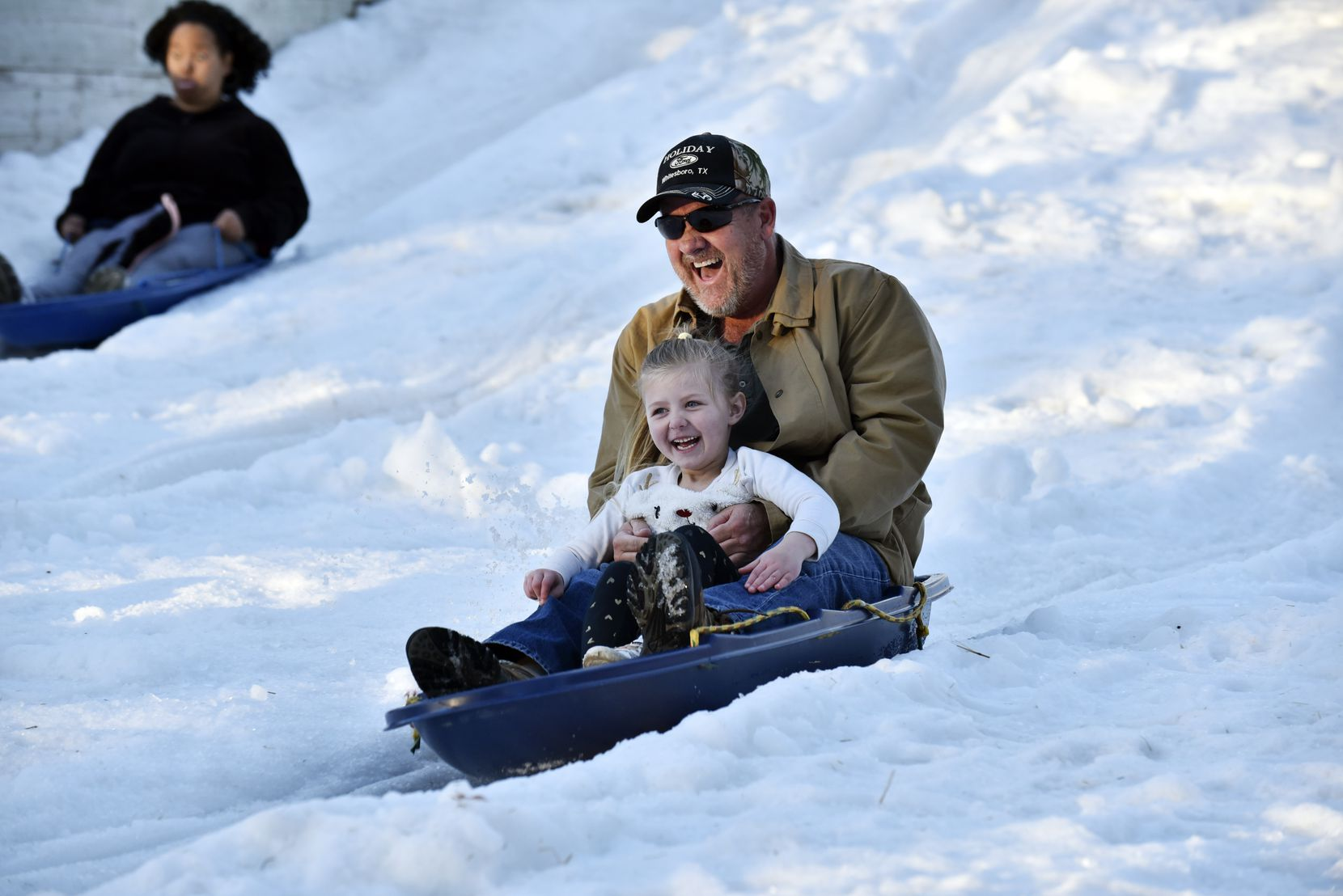 Rodney Allison and his granddaughter ride down a snow hill during Six Flags Over Texas' Holiday in the Park.