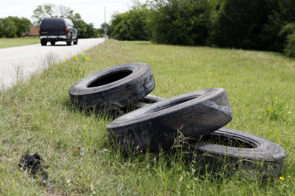 Old tires lay scattered on the side of Gooch Street in South Dallas.