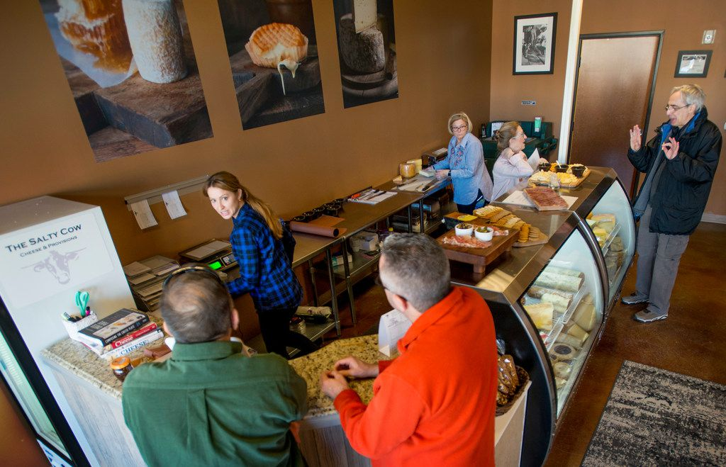 Jennifer Gentry, second from left, who owns The Salty Cow, an artisian cheese shop in Lewisville, Texas, with her husband Harold Gonzalez talks with customers on January 13, 2018.