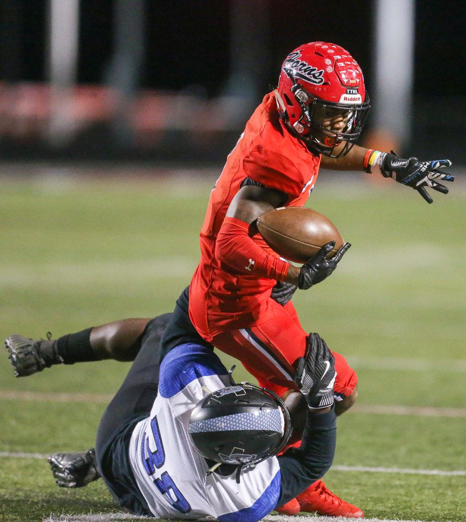 Cedar Hill wide receiver Quin Bright (1) carries the ball as he is defended by Mansfield Summit defensive end Kkennis Emuze (38) during the first half of a high school football game between Cedar HIll and Mansfield Summit on Friday, October 11, 2019 at Longhorn Stadium in Cedar Hill, Texas. (Shaban Athuman/Staff Photographer)