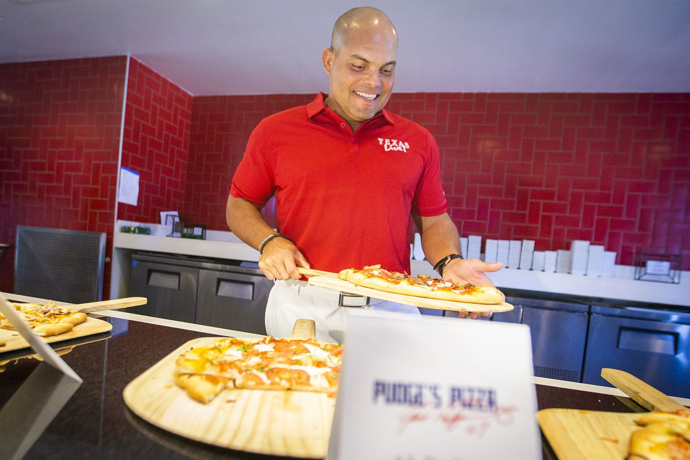 """Hall of Fame Texas Rangers catcher Ivan """"Pudge"""" Rodriguez showed off samples of pizza that will be offered at Pudge's Pizza, a  restaurant at the Texas Live development during a press event at Globe Life Park on Wednesday. He joins former Cowboys quarterback Troy Aikman, who will also have a venue at the center which is set to open in  August."""