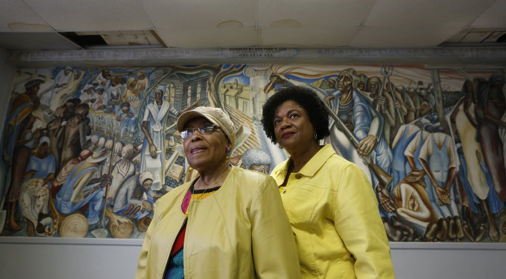 Charlotte Kelly Bryant, president of the Blue Triangle Multi-Cultural Association, and Lucy Bremond with the Blue Triangle Multi-Cultural Association stand in front of Contribution of Negro Women to American Life and Education, a mural damaged by Hurricane Harvey.