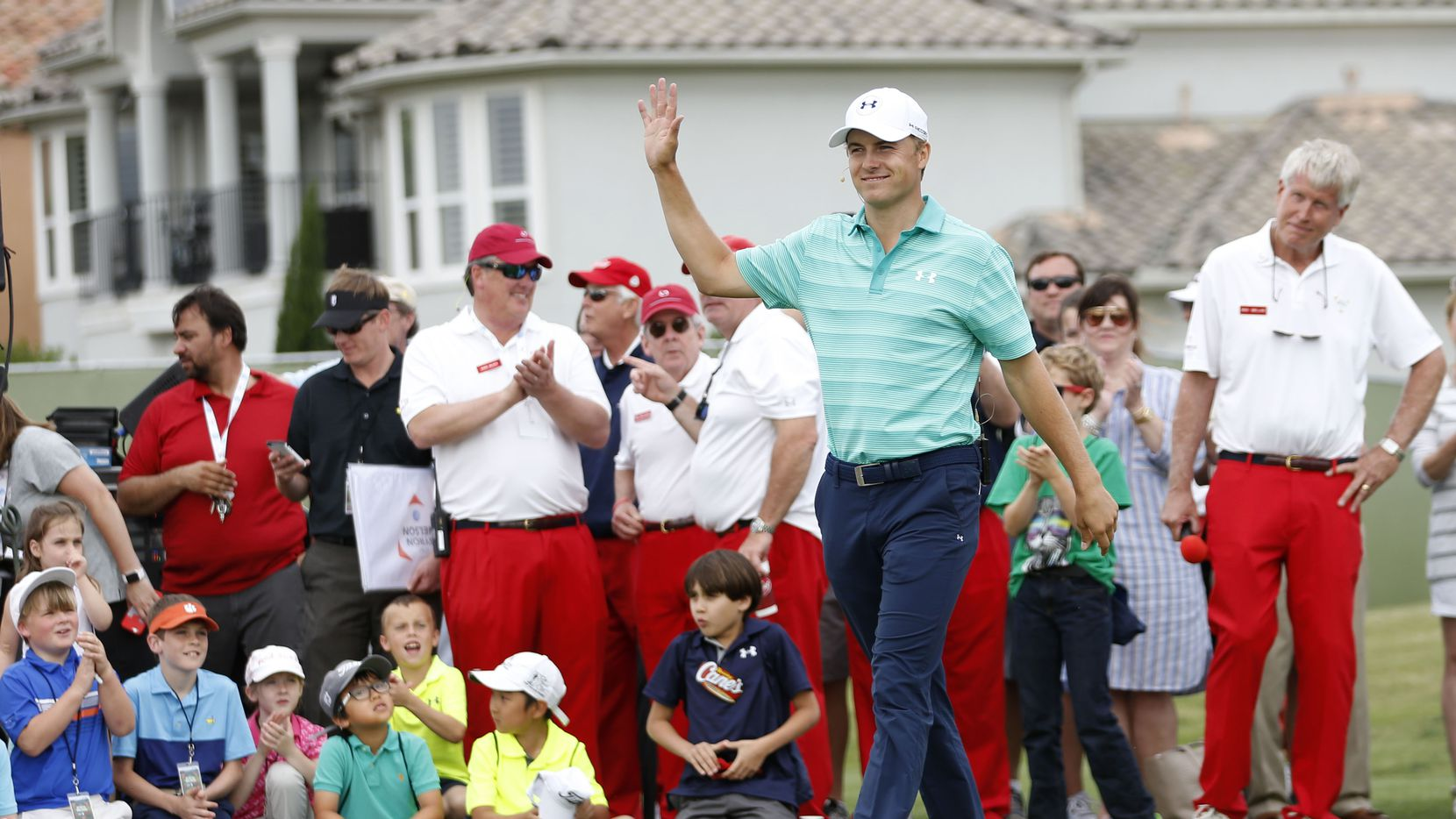 Jordan Spieth waves to the crowd as he is introduced  during a youth golf clinic at TPC Four Seasons in Irving, on Tuesday, May 17, 2016, before last year's Byron Nelson tournament. Behind him are members of the Dallas Salesmanship Club, wearing their trademark red pants.