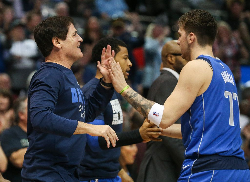 Dallas Mavericks owner  Mark Cuban (left) celebrates a play with forward Luka Doncic during a timeout in the first half a matchup between the Mavericks and the Charolette Hornets on Feb. 6, 2019 at American Airlines Center in Dallas.