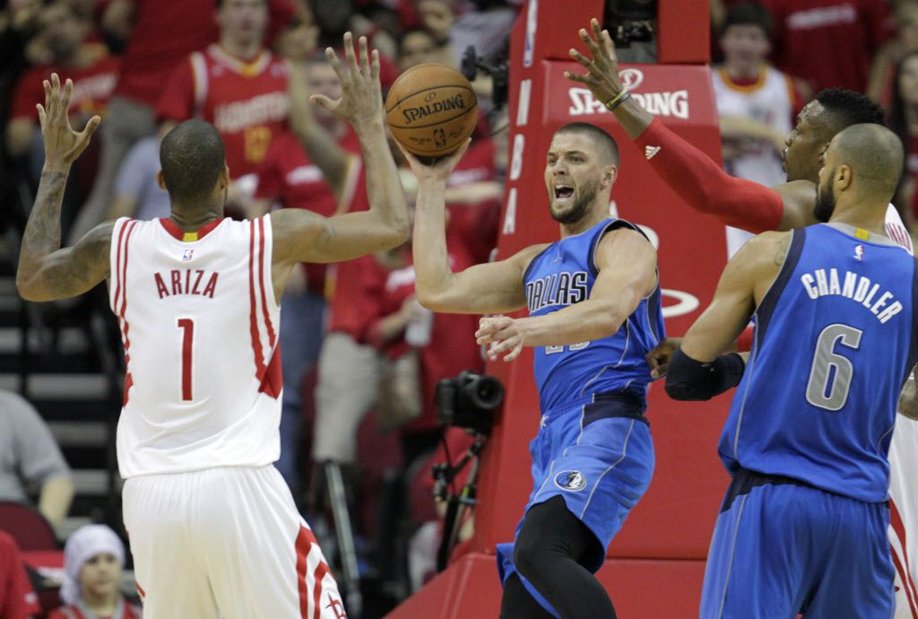 Dallas Mavericks forward Chandler Parsons (25) looks to pass out as he is defended by Houston Rockets forward Trevor Ariza (1) and Houston Rockets center Dwight Howard (12) during the second half of game 1 of the first round of the NBA playoffs at Toyota
