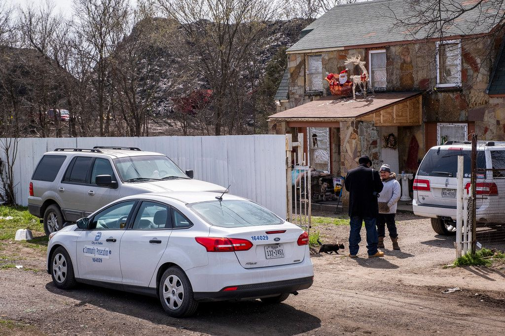 A city of Dallas Community Prosecution and Community Courts Team officer talks with a man living on the property where Blue Star is operating a shingle-recycling company that turns old roofs into asphalt.