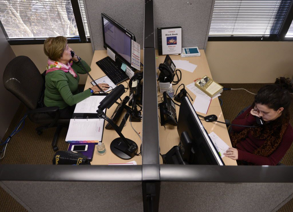 Volunteer Susan Odom (left) and volunteer Catherine Guilbeau answer a phone calls at Contact Line, a crisis hotline in Dallas on Dec. 29, 2014. The hotline, which provides a listening ear for people in crises of all kinds, from suicide to mental illness, is shutting down Dec. 31, 2014 after 47 years because of a lack of funding. (Rose Baca/The Dallas Morning News) 12312014xMETRO