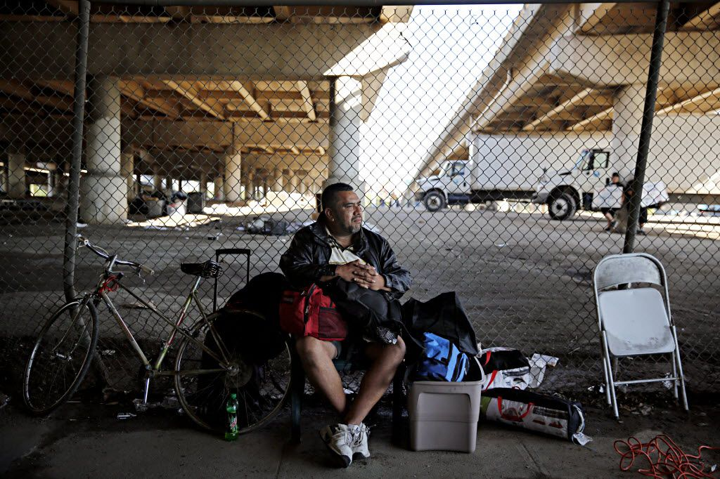 """A man who called himself """"J.R."""" sits with his belongings outside the now gated Tent City Tuesday, May 3, 2016 in Dallas. The final two sections of the contentious homeless encampment where closed Tuesday morning, sending the remaining residents scrambling for shelter. J.R. said he has been living in Tent City for two months."""