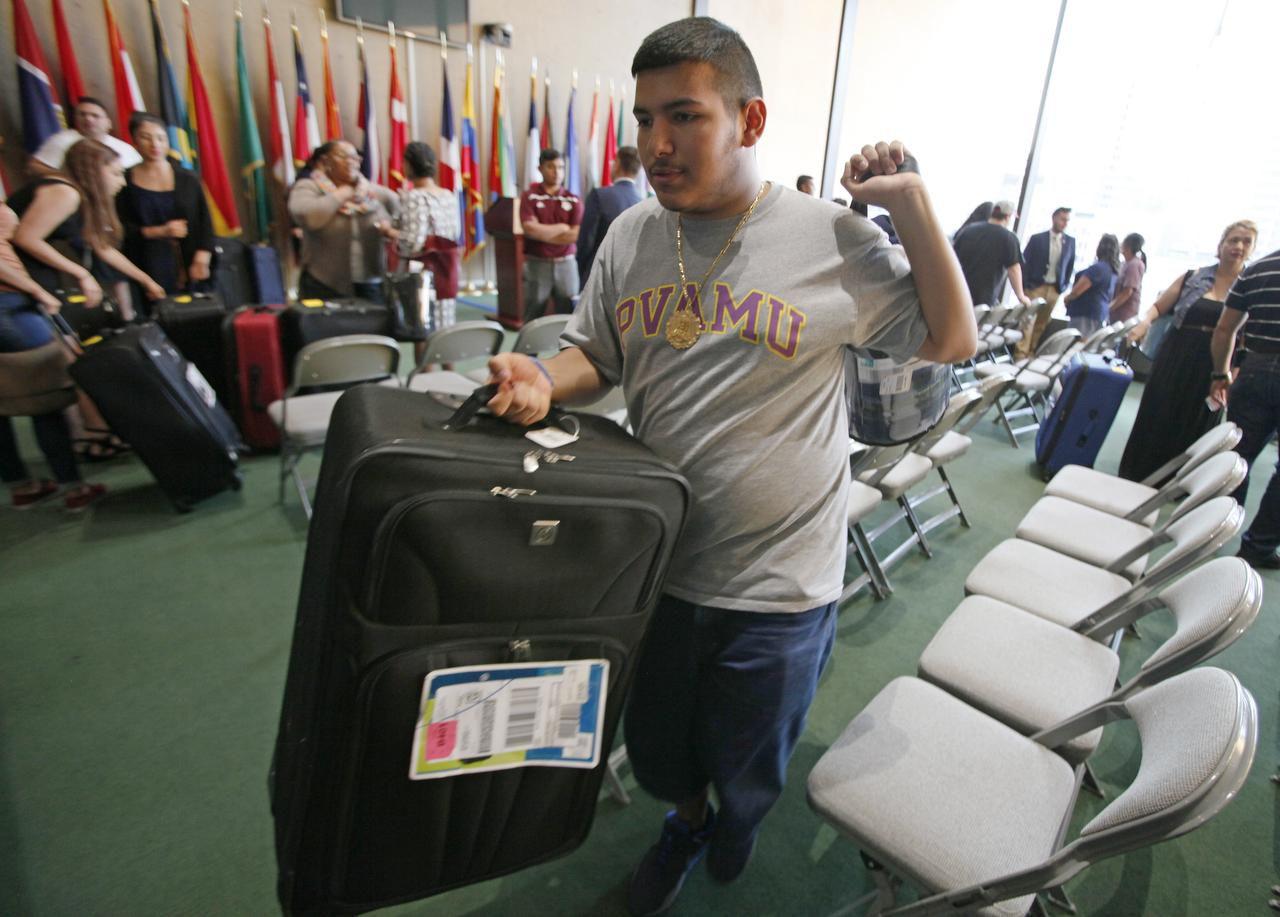 José Sandoval, de 18 años, lleva su maleta y una frazada durante la entrega de equipaje donado en el Dallas City Wide Luggage Drive. Sandoval, egresado de la preparatoria Kimball, estudiará en Prairie View A&M University. (ESPECIAL PARA AL DÍA/BEN TORRES)