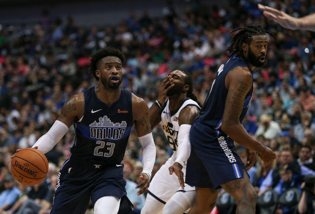 Utah Jazz forward Jae Crowder (99, background center) grimaces after being hit by Dallas Mavericks guard Wesley Matthews (23) on a drive during the second half a game between the Dallas Mavericks and the Utah Jazz at the American Airlines Center in Dallas, Sunday, October 28, 2018. (Ryan Michalesko/The Dallas Morning News)