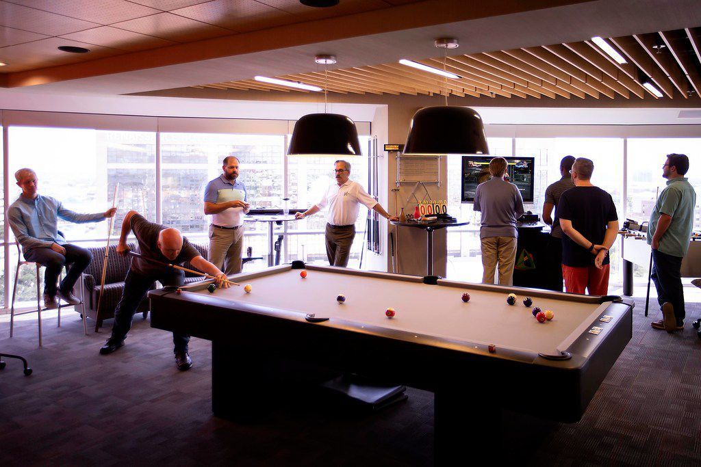 \ Employees play billiards and video games during a party celebrating the month's employee birthdays at Systemware in Addison.