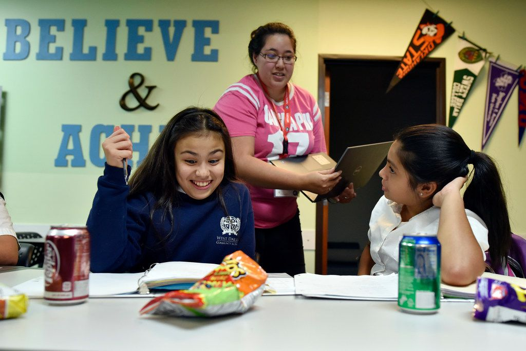 Sixth-graders Mallory Perez (left) and Valerie Perez work on their math homework as mentor Marthaelena Tramel prepares to assist them during the Trinity River Mission after-school program in West Dallas, Monday, Sept. 10, 2018.
