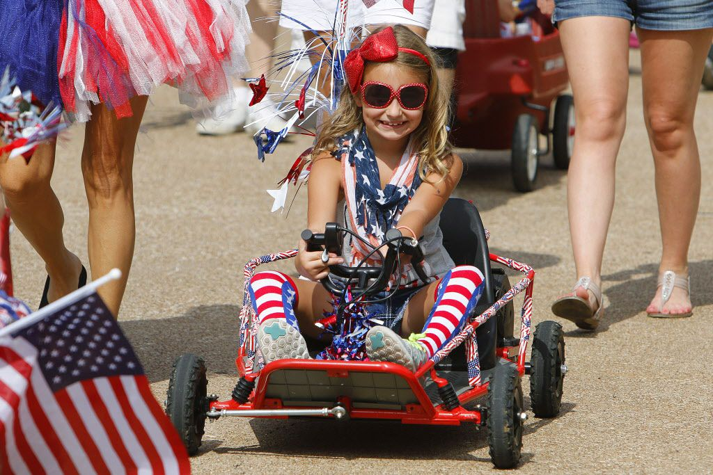 Ashlin Knight, 7, rides her kart down Timber Creek Rd. during the Independence Fest Children's Parade in Flower Mound, Texas on Saturday, July, 4, 2015.