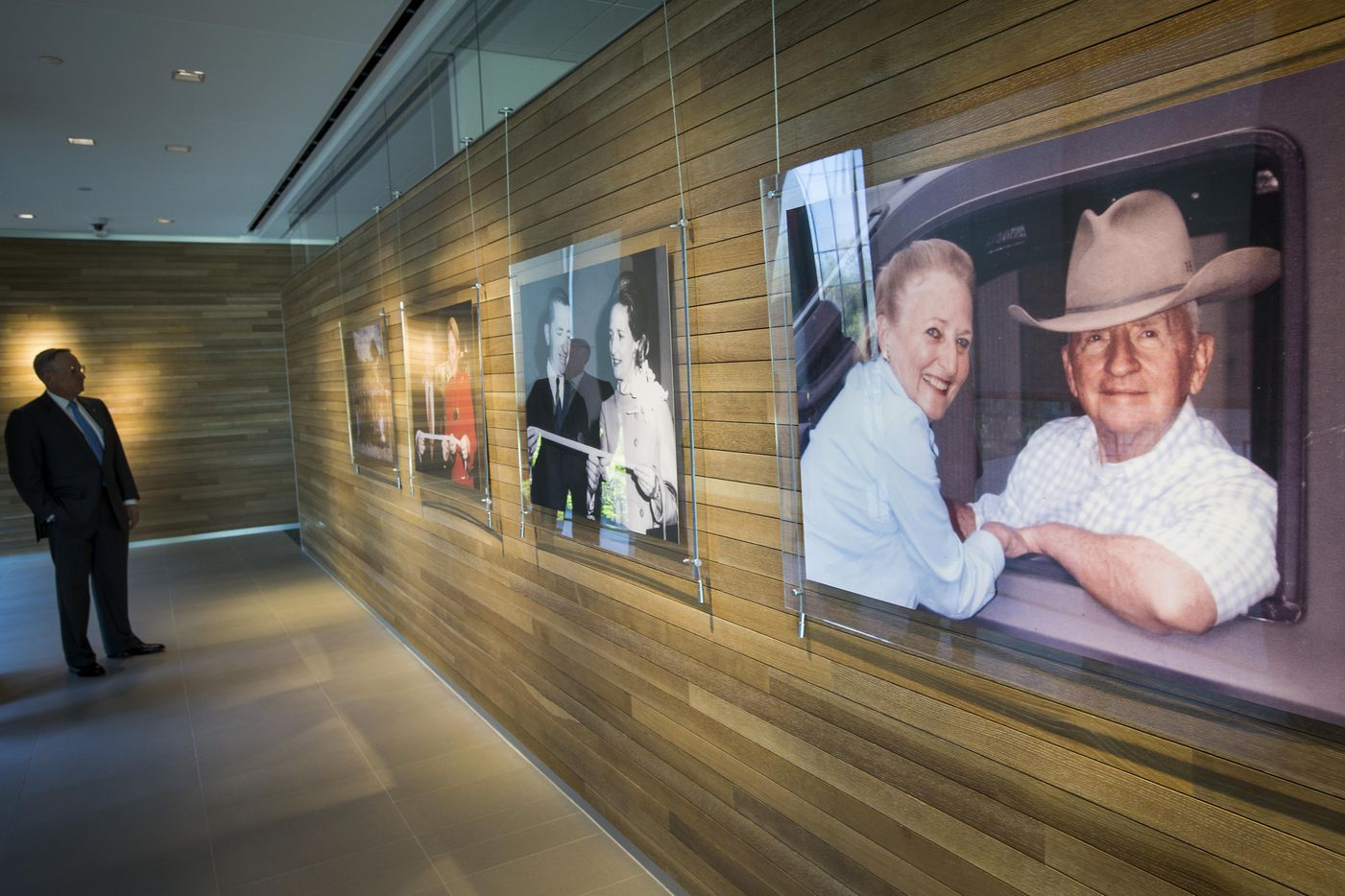 Ross Perot Jr. looks over photographs of his parents while leading a tour of the family's new office headquarters on Turtle Creek.