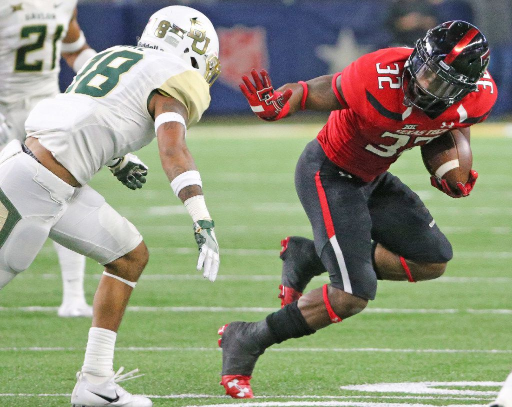 Texas Tech running back Da'Leon Ward (32) gets set to stiff-arm Baylor safety Chance Waz (18) on a third quarter run during the Baylor University Bears vs. the Texas Tech University Red Raiders NCAA football game at AT&T Stadium in Arlington, Texas on Friday, November 25, 2016. (Louis DeLuca/The Dallas Morning News)