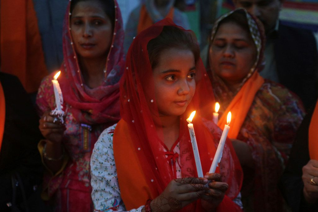 Pakistani citizens light candles at a vigil for the victims of bomb explosions in churches and hotels in Sri Lanka, in Lahore, Pakistan, Tuesday April 23, 2019. The death toll from the Easter Sunday bombings in Sri Lanka, rose Tuesday to more than 300.  (AP Photo/K.M. Chaudary)
