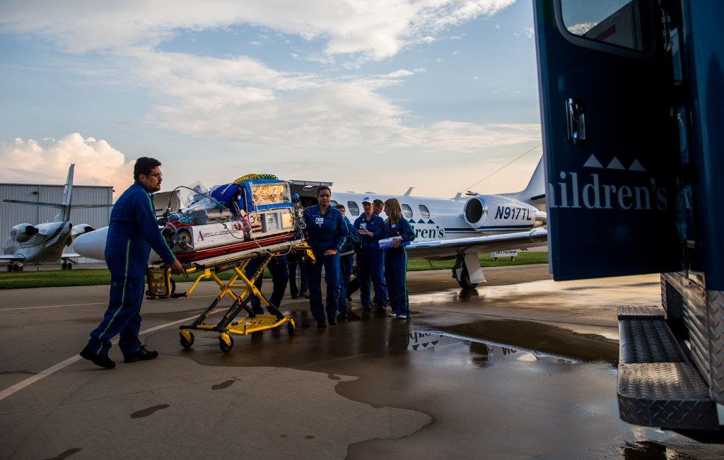 Paramedics transport one of ten babies in a Neonatal Intensive Care Unit from a Cook Children's Hospital airplane to an ambulance on Thursday, August 24, 2017 at Teddy Bear Transport hanger at Fort Worth Meacham Airport in Fort Worth, Texas. The babies were evacuated from Driscoll Children's Hospital in Corpus Christi ahead of Hurricane Harvey.