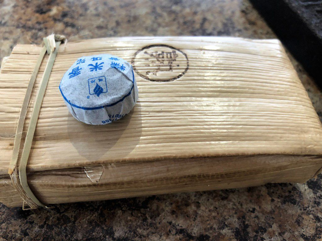 A small coin of Sticky Rice pu'er and a brick of rapidly ripened pu'er at The Cultured Cup.