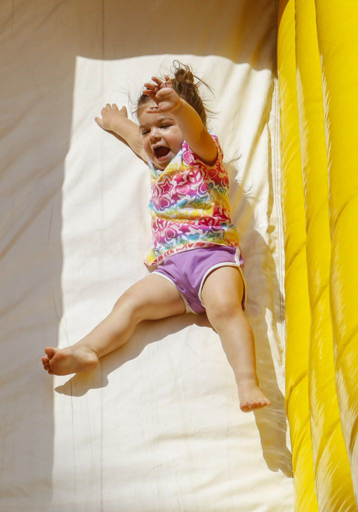 Presley Reynolds, 2, yells as she slides down the slide in the Kidz Korner at the Wildflower! Arts & Music Festival in Richardson, TX on Saturday, May 16, 2015.