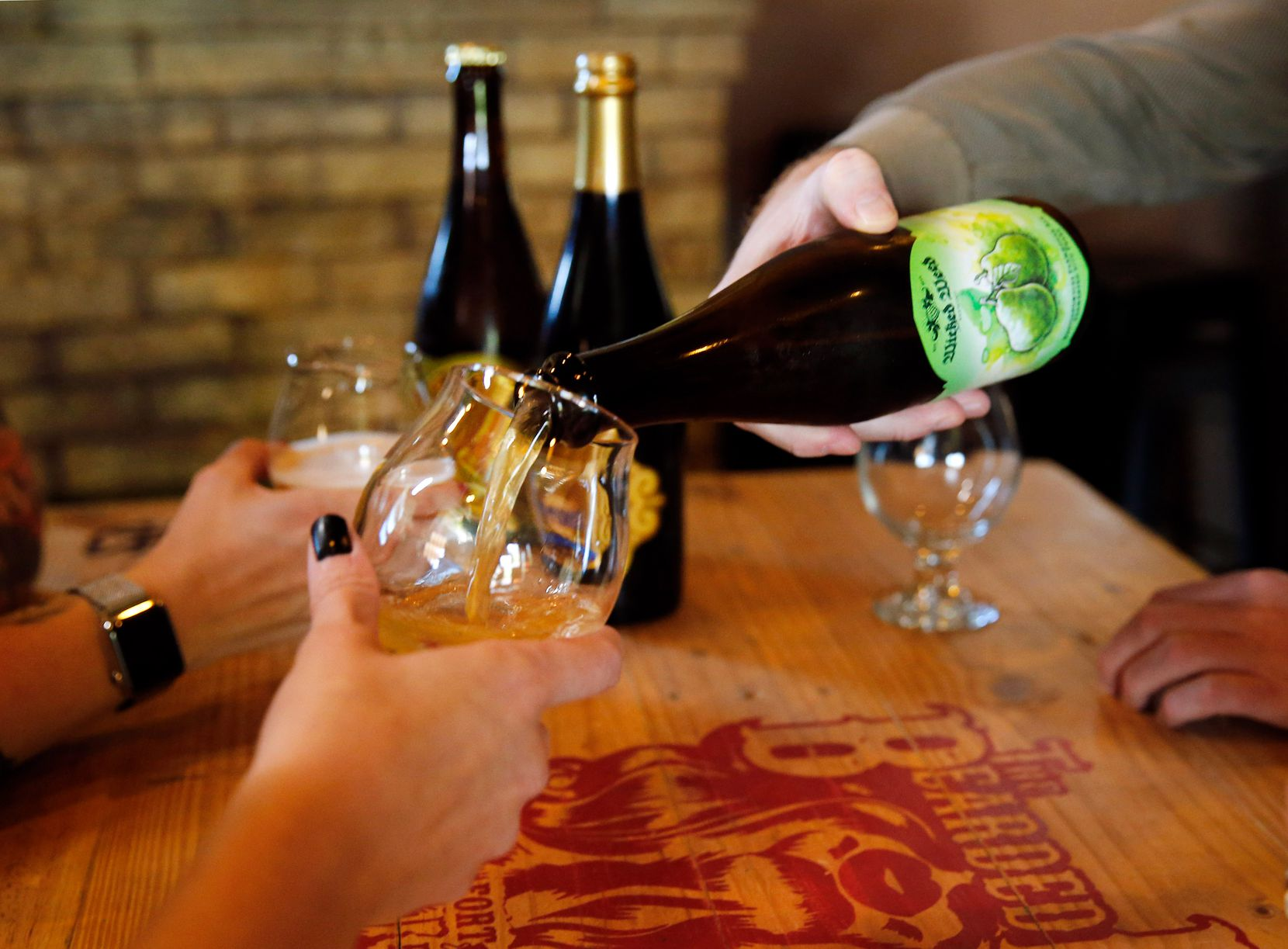 Beer lovers at the Bearded Lady in Fort Worth share a bomber, a large-format bottle of beer. (Tom Fox/The Dallas Morning News)
