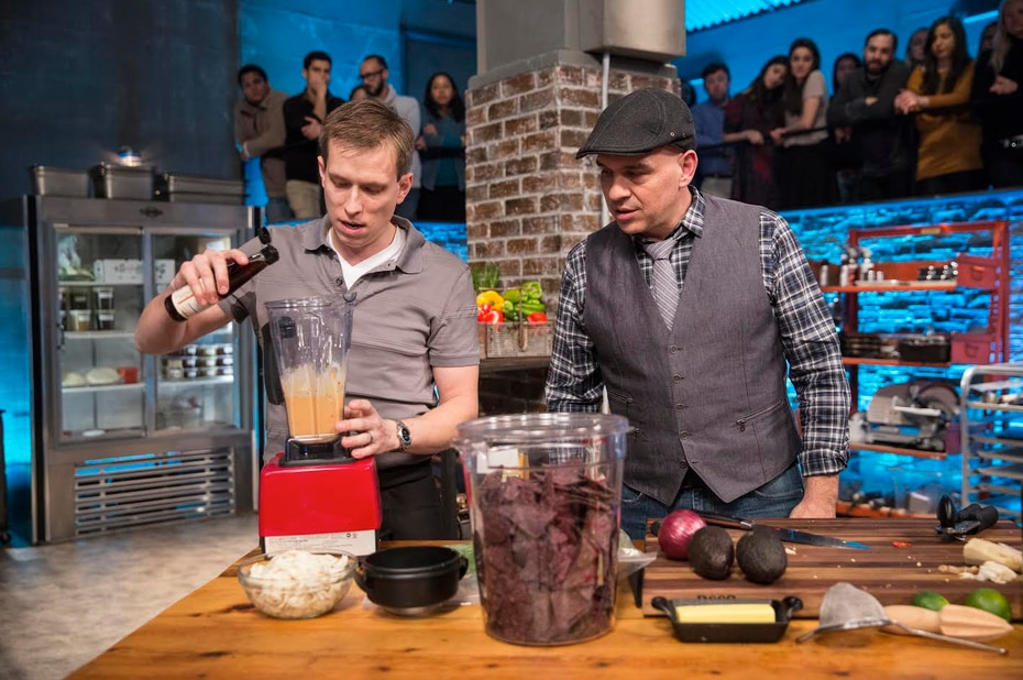 Braden Wages, on left, cooks while chef Michael Symon looks on. Symon and chef Daphne Oz judge the first round on 'Beat Bobby Flay.'