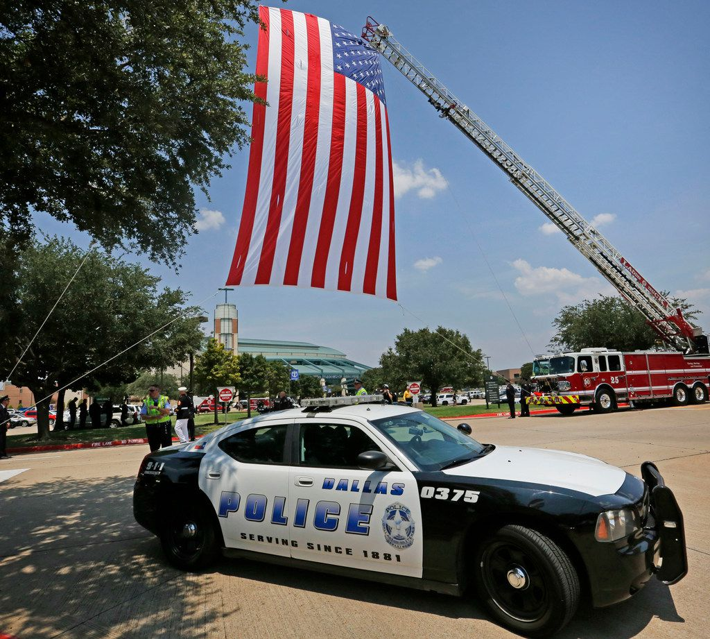 "A Dallas Police cruiser leaves the parking lot after the funeral service for Dallas Police Department Senior Cpl Earl James ""Jamie"" Givens, held at Prestonwood Baptist Church in Plano, Texas on Thursday, July 26, 2018. (Louis DeLuca/The Dallas Morning News)"