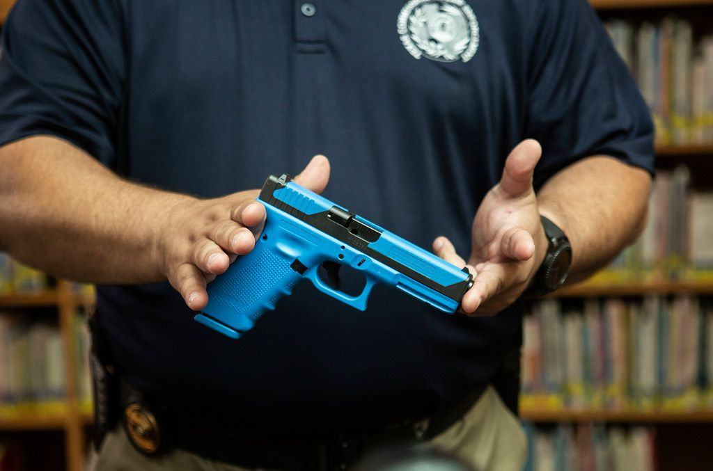 Michael Antu, the Director of Enforcement and Special Services handles a gun that shoots simulated ammunition while talking to the media about what the student school marshals will be using when they perform practice drills during one of the trainings at Windermere Elementary School in Pflugerville, Texas on August 10, 2018. (Thao Nguyen/Special Contributor)