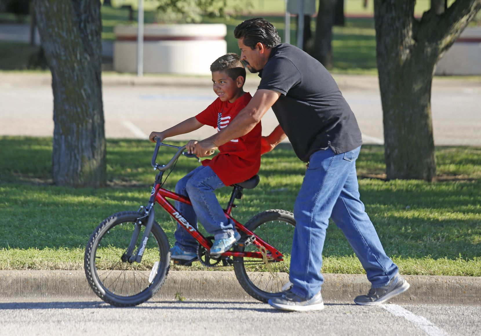 Jose Crispin helps his son, Andrew Garcia, 6, learn to ride his bike at Balch Springs Irwin Park, where vigils were held for 15-year-old  Jordan Edwards, who was shot nearby by a Balch Springs police officer.