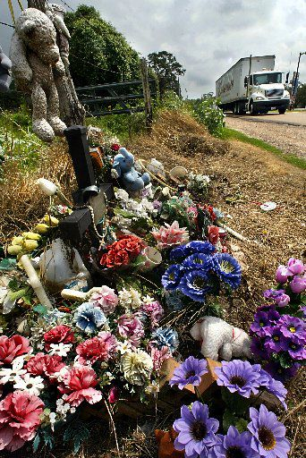 Flowers, teddy bears, water and rosary beads are among the items left in 2004 at the site where 19 illegal immigrants were found dead a year earlier inside of a tractor trailer parked at a truck stop on U.S. Highway 77 in south Victoria.