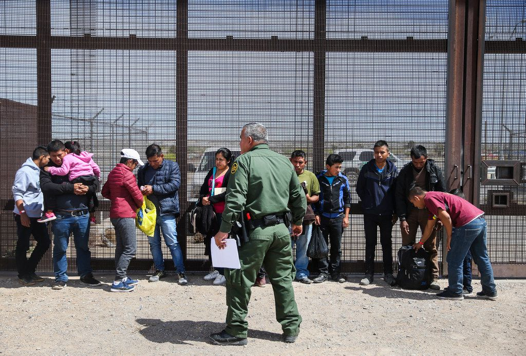 Central American asylum seekers wait as U.S. Border Patrol agents take them into custody after crossing into the United States from Mexico on Thursday, April 4, 2019 in El Paso, Texas.