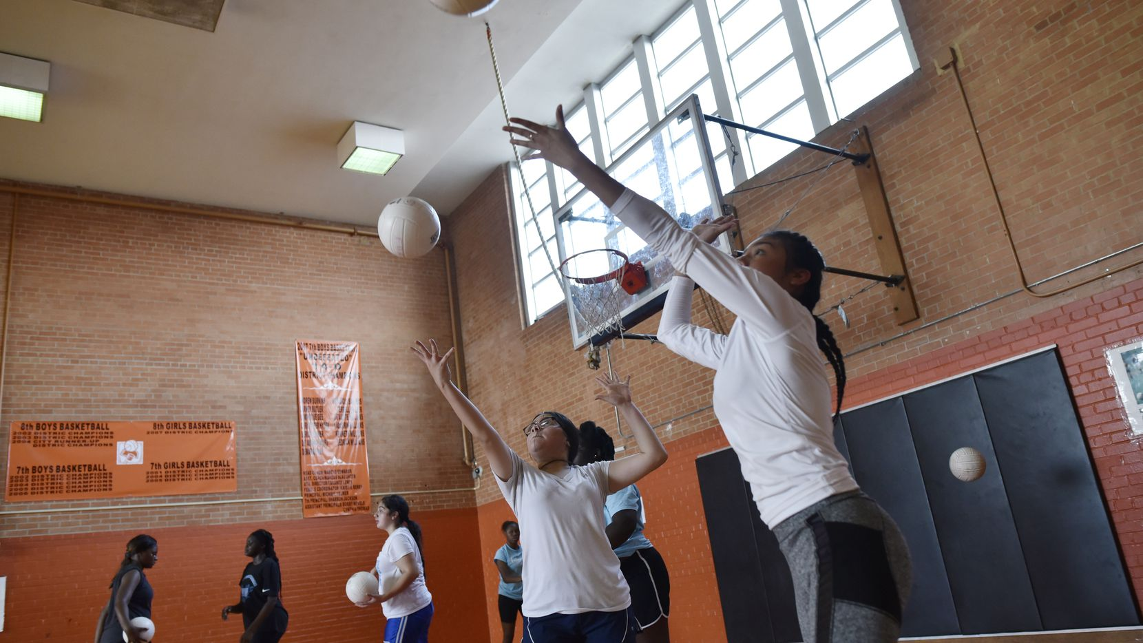 Roosevelt's Vanessa Ortiz (left) and Kate Mar work on their serve during volleyball workouts at Oliver W. Holmes Academy in Dallas. Roosevelt is practicing at the middle school because its high school is being renovated. (Ben Torres/Special Contributor