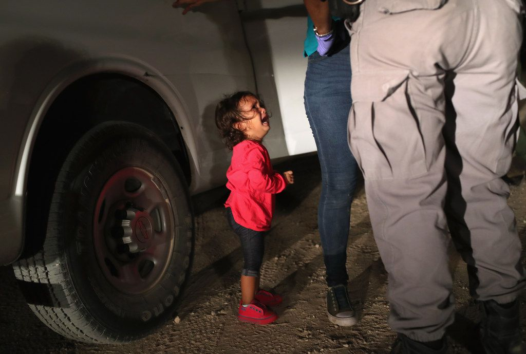 A 2-year-old Honduran asylum seeker cries as her mother is searched and detained near the U.S.-Mexico border on June 12, 2018, in McAllen.