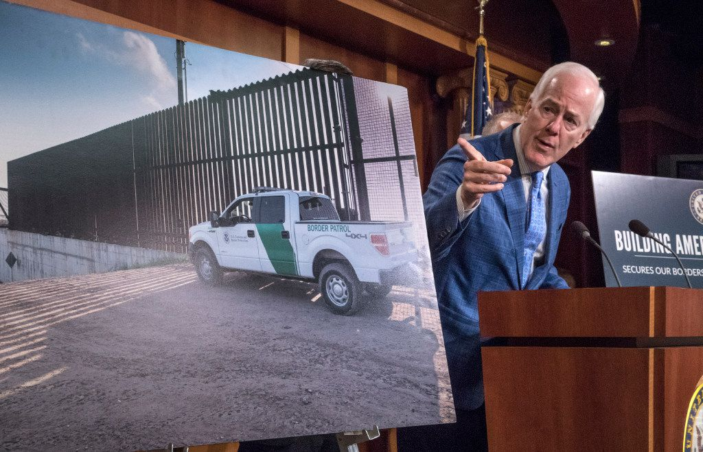 Senate Majority Whip John Cornyn of Texas points to a poster with an image of a barrier on the Texas-Mexico border as he talks to reporters about border security on Thursday, Aug. 3, 2017, on Capitol Hill.