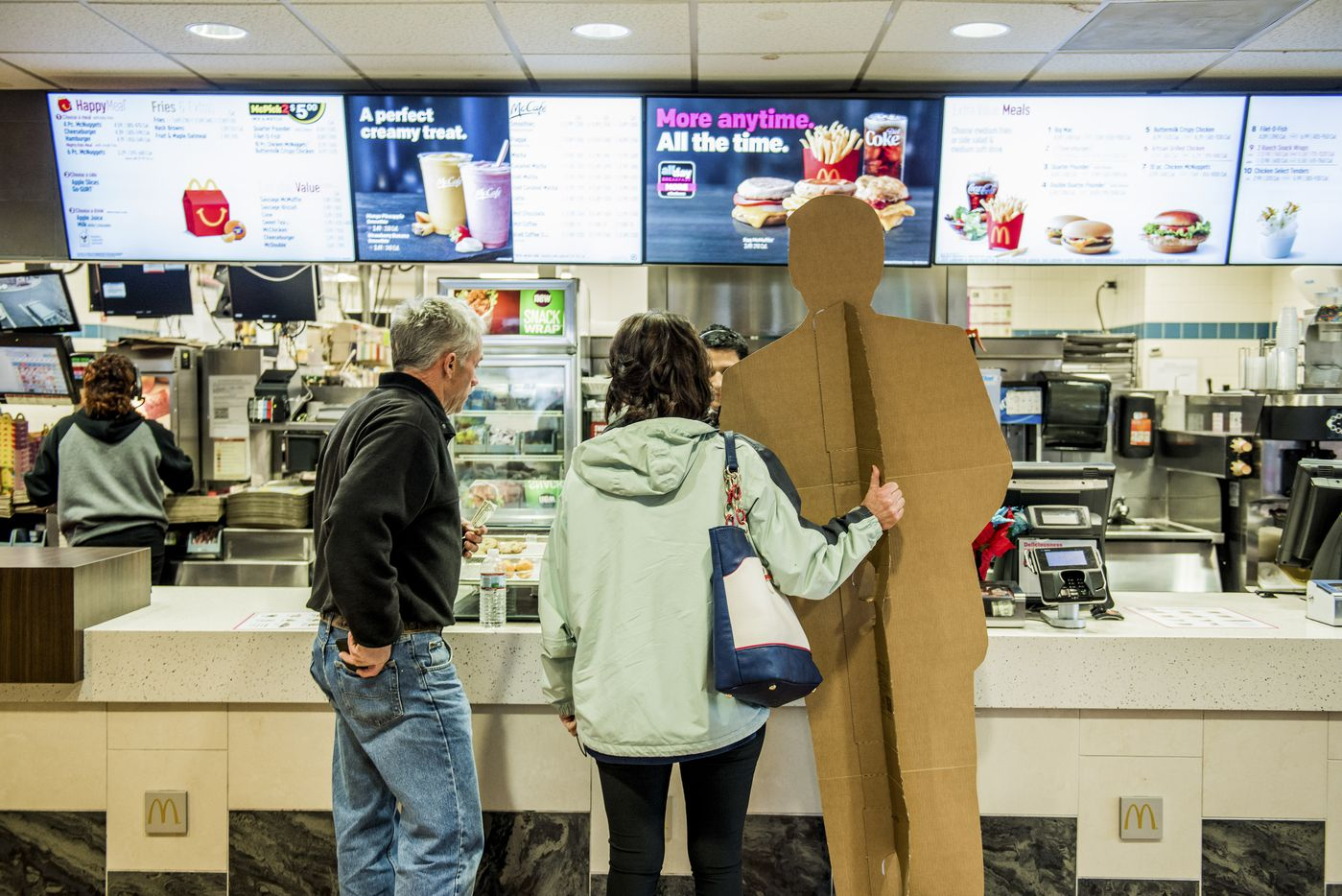 Dianna Ploss holds her Donald Trump cardboard cutout while ordering food with Scott Hayes at a McDonald's in Norwalk, Conn., Jan. 18, 2017. Ploss and her friend, Hayes, drove ten hours to Washington to attend Trump's inauguration.